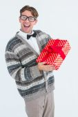 Happy geeky hipster with wool jacket holding present — Stock Photo