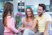 Daughter surprising mother with flowers — Stock Photo