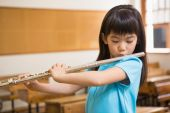 Cute pupil playing flute in classroom — Stock Photo