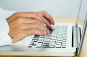 Man using laptop on desk — Stock Photo