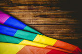 Gay pride flag on wooden table — Stock Photo
