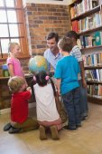 Cute pupils and teacher looking at globe in library — Stock Photo
