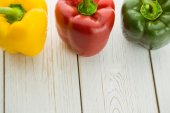 Three peppers on chopping board — Stock Photo