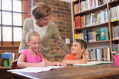 Teacher helping pupils in library — Stock Photo