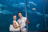 Happy couple using selfie stick — Stock Photo