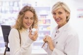 Smiling pharmacist and customer discussing a product — Stock Photo