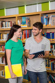Students looking at tablet in the library — Stock Photo