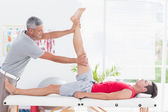 Physiotherapist doing leg stretching to his patient — Stock Photo
