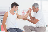 Doctor examining his patient arm — Stock Photo
