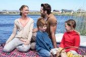 Happy family having picnic at a lake — Stock Photo