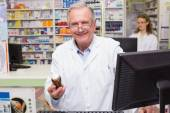 Pharmacist holding medicines looking at camera — Stock fotografie