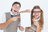 Geeky hipsters pointing at poster — Stock Photo