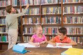 Учитель, ищет книги в библиотеке — Стоковое фото