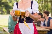 Pretty oktoberfest girl holding beer tankards — Stock Photo