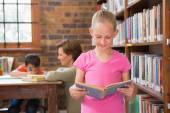 Cute pupil reading in library — Stock Photo