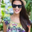 Smiling beautiful brunette wearing straw hat and sun glasses — Stock Photo #73286197