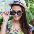 Smiling beautiful brunette wearing straw hat and sun glasses — Stock Photo #73287293
