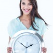 Pretty brunette holding a clock smiling at camera — Stock Photo #73287553