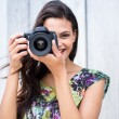 Smiling beautiful brunette taking pictures — Stock Photo #73287889