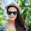 Smiling beautiful brunette wearing straw hat and sun glasses — Stock Photo #73287911