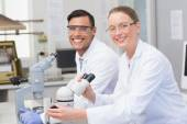 Happy scientists using microscope — Stock Photo