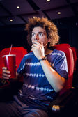 Young man watching a film and drinking soda — Stock Photo