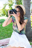 Smiling beautiful brunette sitting on the blanket and taking pic — Stock Photo