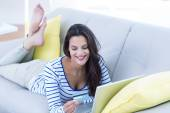 Smiling beautiful brunette doing online shopping on the couch — Stock Photo