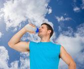 Lachende jongeman drinkwater — Stockfoto