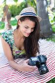 Smiling beautiful brunette lying on the blanket and taking pictu — Stok fotoğraf