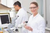 Scientist examining petri dish smiling at camera — Stock Photo