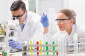 Focused scientists examining test tube — Stock Photo