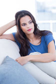 Thoughtful beautiful brunette sitting on the couch — Stock Photo