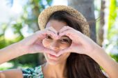 Smiling beautiful brunette doing heart shape with her hands — Stock Photo