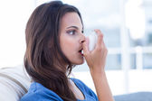 Beautiful brunette using inhaler  — Stock Photo