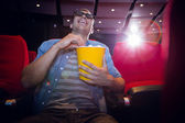 Happy young man watching a 3d film — Stock Photo
