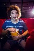 Mladý muž sleduje film a jíst popcorn — Stock fotografie