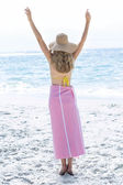 Blonde standing by the sea arms raised — Stock Photo