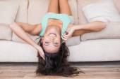 Pretty brunette lying upside down on couch  — Stockfoto