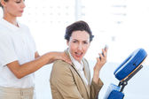 Upset businesswoman having back massage — Stock Photo