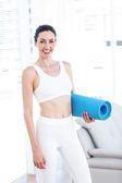 Smiling brunette holding exercise mat — Stock Photo
