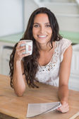 Brunette reading newspaper with a mug — Stock Photo