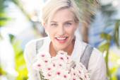 Blonde holding bunch of flowers — Stock Photo