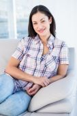 Pretty brunette smiling on couch — Stock Photo