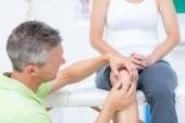 Doctor examining his patients knee — Stock Photo