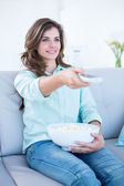 Happy brunette watching television with bowl of popcorn  — Stock Photo