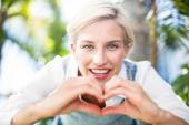 Blonde smiling and doing heart shape — Stock Photo