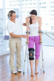 Doctor helping woman walking with crutches — Stock Photo