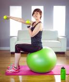 Fit woman lifting dumbbell sitting on ball — Foto Stock