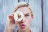 Pretty blonde woman grimacing with cupcake — Stock Photo